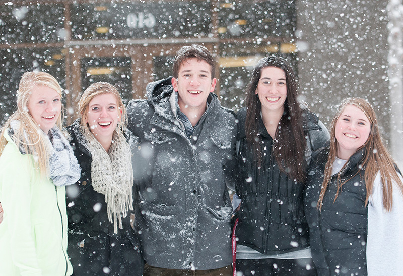 Students pose during a snowfall on campus